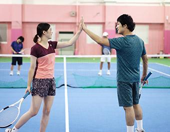 水色の服を着てラケットを持ったコーチと、ピンクの服を着ているスタッフ